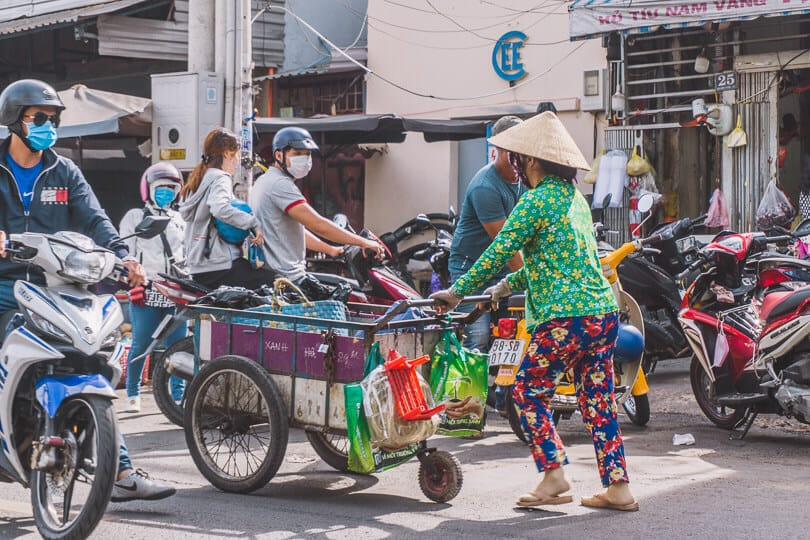 Local pushing a cart in Ho Chi Minh City.